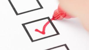 Macro shot of human hand drawing red check mark in checklist box